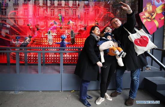 People take selfies with a Christmas window at Printemps department store in Paris, France, Nov. 14, 2019. The city of Paris is decorated with Christmas trees and decorations for the festival season. (Xinhua/Gao Jing)