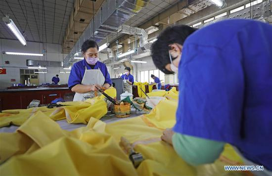 Workers make protective suits at Shenyang Rubber Research & Design Institute Company Ltd. in Shenyang, northeast China's Liaoning Province, Feb. 12, 2020. The company has rushed to work to meet the need of protective suits for the fight against novel coronavirus. (Xinhua/Yang Qing)