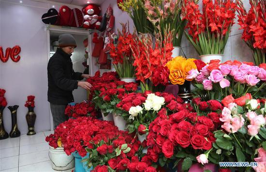 A boy prepares flowers ahead of the Valentine's Day at a flower shop in Kabul, capital of Afghanistan, Feb. 13, 2020. (Xinhua/Rahmatullah Alizadah)