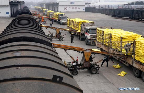 Crew members load spring ploughing materials onto a freight train with conveyers at the Kaifeng Railway Station in Kaifeng, central China's Henan Province, Feb. 13, 2020. The Kaifeng Railway Station, affiliated to China Railway Zhengzhou Group Co., Ltd, has rolled out active precaution measures while organizing crew members to resume work gradually amid the national fight against the novel coronavirus outbreak. A