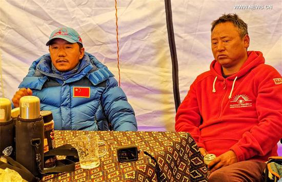Team leader Tselok (L) is seen at the gathering for the announcement of a list who will climb to the peak of Mount Qomolangma at the advance camp at an altitude of 6,500 meters on Mount Qomolangma, May 18, 2020. A Chinese mountaineering team on Monday released a list of 12 people, including two surveyors, who will climb to the peak of Mount Qomolangma. If everything goes smoothly, they will arrive at the peak on May 22 to conduct surveys in gravity, global navigation satellite systems, weather and depths of ice and snow. Chen Gang and Wang Wei, both of whom are surveyors from the Ministry of Natural Resources, are on the list. If either of them manages to arrive at the peak, it will set a record for Chinese surveyors setting foot on the world's highest mountain peak, according to the team. The names of a support squad and a backup squad were also released on Monday. (Xinhua/Lhapa)
