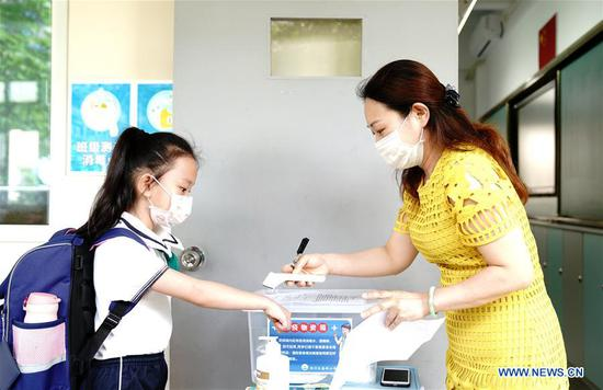 A teacher measures a student's body temperature at a primary school in east China's Shanghai, June 2, 2020. More students in the Shanghai Municipality returned to school as public kindergartens and the first to third grades of primary schools reopened on Tuesday. (Xinhua/Zhang Jiansong)
