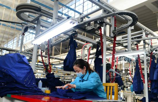 A worker operates on a production line at a garment factory in Jingxing County, Shijiazhuang City of north China's Hebei Province, Feb. 5, 2021. (Xinhua/Jin Haoyuan)