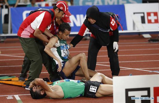 Tariq Ahmed Alamri (C) of Saudi Arabia recieves medical treatment during men's 5000m final of athletics at the 18th Asian Games in Jakarta, Indonesia on Aug. 30, 2018. (Xinhua/Wang Lili)