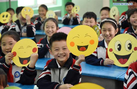 Pupils demonstrate smiley cards to greet the upcoming World Smile Day at a primary school in Handan, north China's Hebei Province, May 7, 2019. World Smile Day is celebrated on May 8 every year. (Xinhua/Hao Qunying)