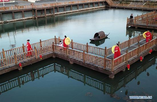 Aerial photo taken on Nov. 10, 2019 shows villager models walking on the wooden trestle of a park in Houtaizi Village of Qian'an City, north China's Hebei Province. The local government made great efforts to improve the rural living environment this year. After high-standard transformation and construction, a rubbish disposal pit has been turned into a beautiful park with clear water and antique buildings, becoming an attractive public place for recreation and entertainment. (Xinhua/Jin Liangkuai)