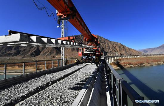 Workers of China Railway 11 Bureau Group Co., Ltd. lay steel rail for a bridge crossing the Yarlung Zangbo River of Lhasa-Nyingchi railway in Sangri County of Shannan, southwest China's Tibet Autonomous Region, Dec. 1, 2019. The rail-laying work of a 4,615-meter-long bridge crossing the Yarlung Zangbo River of Lhasa-Nyingchi railway was completed on Sunday. The Lhasa-Nyingchi railway features complex geological conditions, with a total length of 435 km, 75 percent of which are bridges and tunnels. The construction work began in 2015 and is expected to be completed in 2021. (Xinhua/Chogo)
