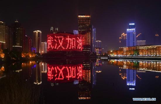 Photo taken on Jan. 31, 2020 shows buildings illuminated with slogans reading