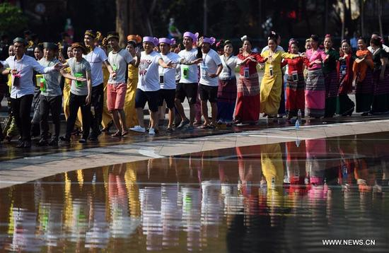 People dance to celebrate the water-sprinkling festival at a square in Jinghong City, Dai Autonomous Prefecture of Xishuangbanna, southwest China's Yunnan Province, April 15, 2018. People sprinkle water to each other to pray for good fortune during the traditional water-sprinkling festival, which is also the New Year festival of the Dai ethnic group. (Xinhua/Wang Changshan)