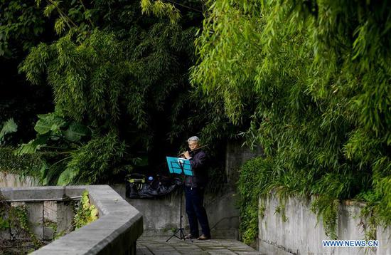 An old man practices playing the flute on the 3rd footpath in Yuzhong district of Chongqing, southwest China, Dec. 2, 2018. Since 2016, local authority has rolled out plans to renovate 14 footpaths with a total length of 39.5 kilometers. The 14 footpaths linking Chongqing's natural and cultural highlights provide visitors the city's most beautiful and important sights. (Xinhua/Liu Chan)