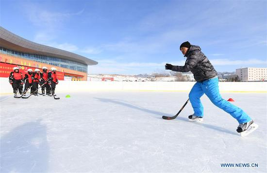 Guo Zhihao (R), coach from Qiqihar Winter Sports Administration Center, trains the players of ice hockey team of Wenyun County Primary School in Fuyun County of Altay, northwest China's Xinjiang Uygur Autonomous Region, Jan 18, 2019. Wenyun County Primary School established their ice hockey team in 2013, the first campus ice hockey team in Altay, with the help of the Charles Wang Ice Hockey Hope Project. There are 50 players aging 10 to 14 in the team at present. Altay is enhancing local winter sports and fitness programs for its rich ice and snow resources, such as ice hockey, ice soccer, skiing and skating. (Xinhua/Sadat)