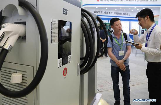 A staff member (R) introduces an electric vehicle charging pole to a visitor during the 2019 Shanghai International New Energy Vehicle Industry Expo in east China's Shanghai Municipality, Aug. 28, 2019. The three-day event opened at Shanghai New International Expo Center on Wednesday with the participation of over 500 global exhibitors. (Xinhua/Fang Zhe)