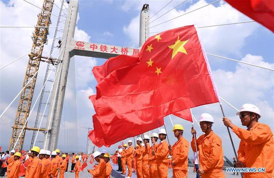 Workers attend a ceremony marking the completion of the main structure of the Pingtan Strait Road-rail Bridge in southeast China's Fujian Province, Sept. 25, 2019. China on Wednesday completed the main structure of the world's longest cross-sea road-rail bridge in Fujian. The last steel girder, weighing 473 tonnes, was bolted on the Pingtan Strait Road-rail Bridge, another mega project in China, on Wednesday morning. With a staggering span of 16.34 km, the bridge connects Pingtan Island and four nearby islets to the mainland of Fujian Province. (Xinhua/Lin Shanchuan)