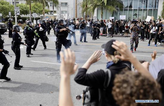 Protesters confront the police during a massive street protest over the killing of George Floyd in Los Angeles, the United States, May 30, 2020. Over 530 people were arrested Friday night and early Saturday after protests against police brutality turned violent in downtown Los Angeles, authorities said Saturday noon. Los Angeles Mayor Eric Garcetti announced at a press conference Saturday afternoon that a curfew will be in effect in the city's downtown beginning from 8 p.m. Saturday to 5:30 a.m. Sunday local time. (Xinhua)