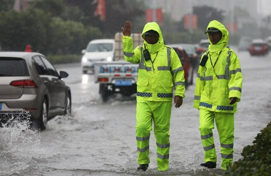 Policemen direct traffic at a waterlogged area in Wuzhi County, central China's Henan Province, July 20, 2021. (Photo by Feng Xiaomin/Xinhua)