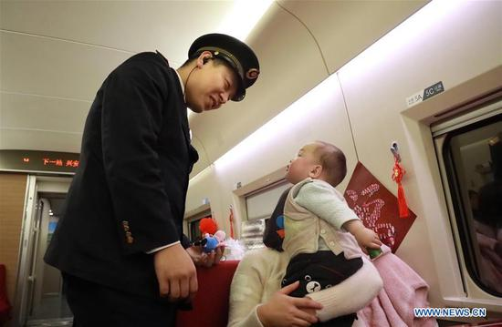 Train conductor Yin Li comforts a baby aboard the high-speed train G529, Feb. 1, 2019. Bullet Train G529/530 runs over 15 hours, the longest travel time of China's high-speed railway, between China's capital Beijing and Beihai of south China's Guangxi Zhuang Autonomous Region. The railway line covers a total length of about 2,675 kilometers. Train conductor Yin Li, a 30-year-old army veteran, is strict with himself and his colleagues. He inspects the bullet train G529/530 every day to ensure travel safety. (Xinhua/Xing Guangli)