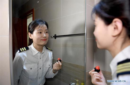 Jiang Dandan makes up before going to work in Yanliang District of Xi'an, capital of northwest China's Shaanxi Province, on March 5, 2019. Jiang Dandan, 29, is one of the youngest test pilots in China and the only female test pilot for commercial transport aircrafts currently being trained at the Aviation Industry Corporation of China, Ltd. She went through dozens of professional courses and 750 hours of flying practice in six years. At the end of 2017, she became a test pilot and participated in the test flights during the research and development of ARJ21-700, C919 and other types of aircrafts. (Xinhua/Liu Xiao)