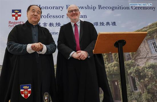 Regent's Park College principal Robert Ellis (R) poses with Chinese writer and Nobel laureate Mo Yan during the Honorary Fellowship Recognition Ceremony at University of Oxford, Britain, on June 12, 2019. Mo Yan was awarded Wednesday the Honorary Fellowship by Regent's Park College, University of Oxford, in recognition of his contribution to Chinese and world literature. The college principal Robert Ellis presented the gown and stole to Mo at the ceremony. They unveiled together a new international writing center named after Mo. (Xinhua/Han Yan)