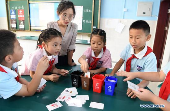Pupils take part in a garbage classification game at Jianping Experimental Primary School in Hefei, capital of east China's Anhui Province, July 11, 2019. The primary school held activities to teach children garbage classification knowledge on Thursday. (Xinhua/Liu Junxi)
