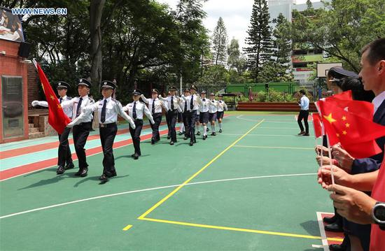 A flag raising team formed by several middle schools escorts the Chinese national flag during a flag raising ceremony at a middle school in Yuen Long of New Territories, Hong Kong, south China, Aug. 11, 2019. The Association of Hong Kong Flag-guards held a flag raising ceremony at a middle school on Sunday. (Xinhua/Wu Xiaochu)
