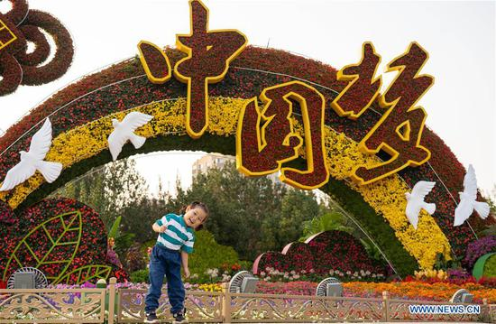 A girl poses for a photo in front of a flowerbed in Beijing, capital of China, Sept. 28, 2019. Flowerbeds were built along the Chang'an Avenue to celebrate the 70th anniversary of the founding of the People's Republic of China. (Xinhua/Cai Yang)