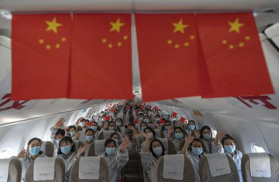 Medical workers from Yunnan Province wave to bid farewell on the plane at Tianhe International Airport in Wuhan, central China's Hubei Province, March 18, 2020. (Xinhua/Fei Maohua)