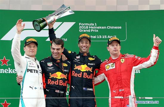 First-placed Red Bull's driver Daniel Ricciardo (2nd R) of Australia, second-placed Mercedes' Valtteri Bottas (1st L) of Finland and third-placed Ferrari's Kimi Raikkonen (1st R) of Finland celebrate on the podium during the awarding ceremony of the Formula One Chinese Grand Prix in Shanghai, east China, April 15, 2018. Daniel Ricciardo claimed the title of the event in 1 hour, 35 minutes and 36.380 seconds. (Xinhua/Fan Jun)