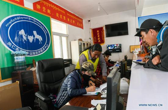 Staff member work at a service center for yak transportation in Ali Prefecture, southwest China's Tibet Autonomous Region, June 27, 2018. Gangsha Village is located at the foot of Mount Kangrinboqe, a sacred Hindu and Buddhist site in Ali. Since the 1980s, local farmers and herdsmen have started to receive pilgrims and tourists from home and abroad. They upgraded services of tourism industry in the past 30 years, and tourism increased villagers' income. (Xinhua/Liu Dongjun)