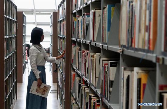 A girl searches books in Zhengzhou library in Zhengzhou, capital of central China's Henan Province, July 31, 2018. The library is packed with readers during the summer vacation. (Xinhua/Li An)