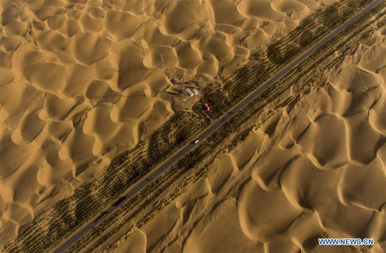 Aerial photo taken on Sept. 27, 2016 shows the Tarim Desert Highway in northwest China's Xinjiang Uygur Autonomous Region. As an important link of the Silk Road Economic Belt, Xinjiang is speeding up the development of transportation and logistics to connect east and west. By the end of 2017, the total length of roads in Xinjiang reached 186,000 km, with 4,578 km of expressways. (Xinhua/Jiang Wenyao)