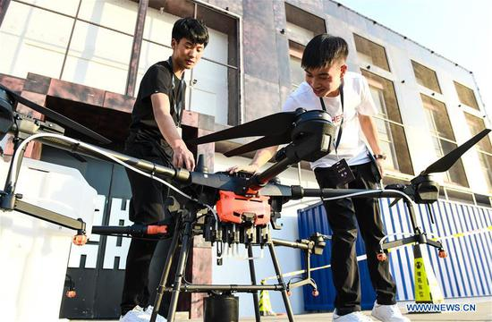 A visitor gets to know more about Chinese drone maker DJI's latest crop protection drone, the T20, at a product launch event in Shenzhen, south China's Guangdong Province, Nov. 5, 2019. Besides the new T20 crop protection drone, DJI also introduced an upgraded version of the drone's spray system as well as appertaining service and training plans on Tuesday. (Xinhua/Mao Siqian)