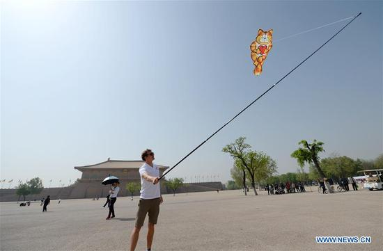 A participant flies a kite at Daming Palace National Heritage Park in Xi'an, capital of northwest China's Shaanxi Province, April 3, 2018. A kite festival kicked off Tuesday here in Xi'an. (Xinhua/Li Yibo)