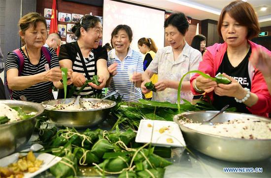 Volunteers make zongzi, a pyramid-shaped dumpling made of glutinous rice wrapped in bamboo or reed leaves, for the elderly persons of no family to celebrate the Duanwu Festival at a community in Zhenjiang City, east China's Jiangsu Province, June 11, 2018. (Xinhua/Shi Yucheng)