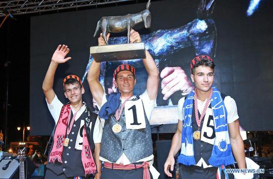 First-place winner Angelino Perkov (C), runner-up Roko Spanja (R) and third-place winner Jakov Popov (L) pose during the 51st traditional donkey races in Tribunj, Croatia, on Aug. 1, 2018. The event which dates back to 1950s features donkey-riders in traditional costumes racing around the village of Tribunj. (Xinhua/Dusko Jaramaz)