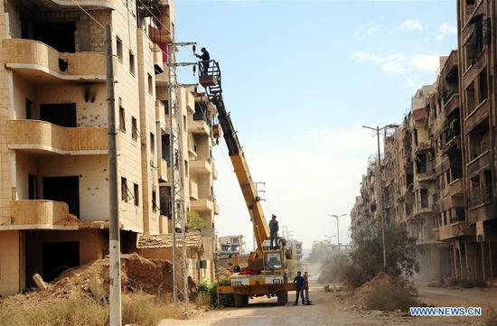 Electricity workers fix power lines in Daraya, suburb in the southwestern countryside of Damascus, Syria, on Oct. 9, 2018. Many Syrians have returned home in Daraya and started to resume life here. The move came after the Syrian government finished the rehabilitation process of the infrastructure in Daraya, which was recaptured by the Syrian army in 2016. (Xinhua/Ammar Safarjalani)