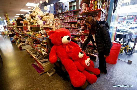 A woman selects a gift for the Valentine's day at a gift shop in Beirut, Lebanon, Feb. 13, 2020. (Photo by Bilal Jawich/Xinhua)