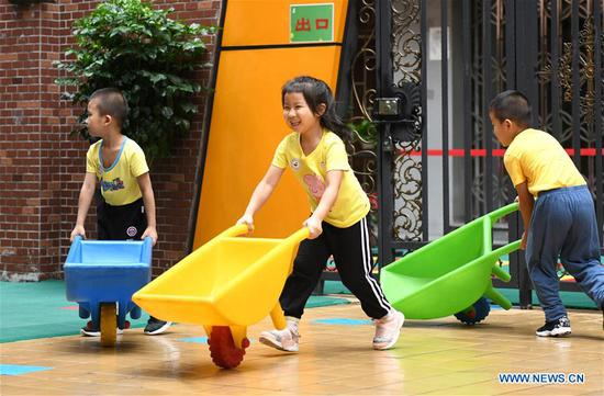 Children play with toy wheelbarrows at Taoyuan Kindergarten in Liwan District of Guangzhou, south China's Guangdong Province, June 2, 2020. Kindergartens in Guangdong Province have begun to reopen on Tuesday as the impact of COVID-19 ebbs away. (Xinhua/Lu Hanxin)