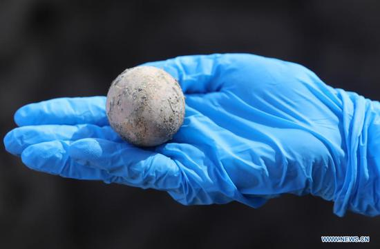 An Israeli archeologist shows an intact chicken's egg of roughly 1,000 years ago in Yavne, central Israel, on June 9, 2021. Israeli archeologists have discovered an intact chicken's egg of roughly 1,000 years ago, the Israel Antiquities Authority (IAA) said Wednesday. The egg was found in an excavation site in Yavne, in a cesspit dating from the Islamic period. (Photo by Gil Cohen Magen/Xinhua)