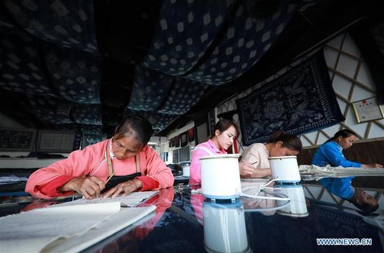 Artists make batik at an experiencing house in Danzhai County, southwest China's Guizhou Province, April 9, 2018. Relying on its intangible cultural heritage, Danzhai encourages local people to develop the business such as opening experience houses for visitors. This also becomes a means of helping local people get rid of poverty with this
