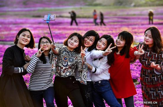 Tourists pose for photos among lantana camara blossoms in Chuancang Village, Taiyang Township, Huoshan County of east China's Anhui Province, April 11, 2018. (Xinhua/Tao Ming)