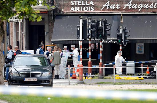 Police officers and forensics experts are seen at the scene of a shooting in Liege, Belgium, on May 29, 2018.