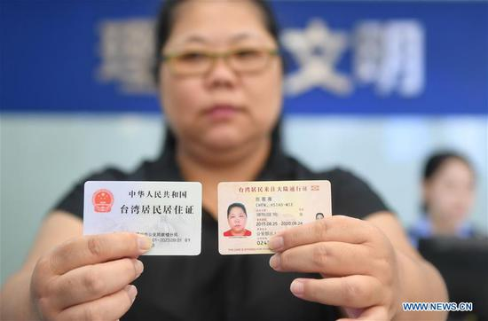 A Taiwan resident living in the Chinese mainland displays the residence permit(L) at Nanjie police station of Gulou Branch of Fuzhou Municipal Public Security Bureau in Fuzhou, southeast China's Fujian Province, Sept. 3, 2018. A new regulation on the application and granting of residence permits for Hong Kong, Macao, and Taiwan residents living in the Chinese mainland was put into effect on Sept. 1. (Xinhua/Lin Shanchuan)