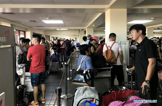 Chinese tourists wait to fly back home in Saipan, the Commonwealth of the Northern Mariana Islands (CNMI), Oct. 28, 2018. Some 1,500 Chinese tourists trapped in Saipan by Super Typhoon Yutu started to fly back home on Sunday. (Xinhua)