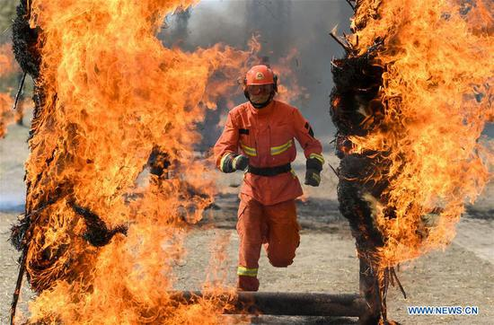 A newly-recruited fireman runs through a fire wall during a training in Hohhot, north China's Inner Mongolia Autonomous Region, June 5, 2019. Over 1,100 socially-recruited firemen are receiving a six-month training in Hohhot. (Xinhua/Peng Yuan)
