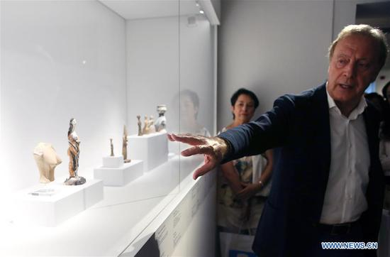 "Nicholas Stampolidis (R), director of the Museum of Cycladic Art, guides visitors at the media preview of ""Picasso and Antiquity. Line and Clay"" at the Museum of Cycladic Art in Athens, Greece, June 19, 2019. A rare exhibition about Pablo Picasso and his inspiration from ancient Greek art is to open here at the Museum of Cycladic Art on Thursday. (Xinhua/Marios Lolos)"