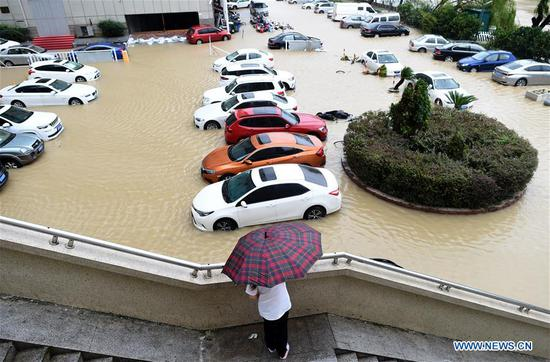 Cars are stranded on a waterlogged parking lot in Wenling, east China's Zhejiang Province, Aug. 10, 2019. China's National Meteorological Center issued an orange alert for Typhoon Lekima on Saturday morning, as it landed in east China's Zhejiang Province. At around 1:45 a.m., the center of Typhoon Lekima, the ninth typhoon of the year, made landfall in the city of Wenling in Zhejiang, with a maximum wind force of 187 km/h. The super typhoon weakened to a typhoon at 5 a.m. at a maximum wind force of 144 km/h. (Xinhua/Han Chuanhao)