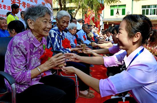 Young people serve tea to express respect for the elderly during celebrations for the Chongyang Festival in Xijiao Village of Xingtian Township of Wuyishan City, southeast China's Fujian Province, Oct. 7, 2019. A series of events were held on Monday to celebrate Chongyang Festival, which falls on the ninth day of the ninth Chinese lunar month, a day to pay respect to seniors in China. (Xinhua/Zhang Guojun)