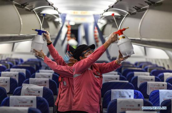 Staff members disinfect the cabin of an airplane after its arrival at the Haikou Meilan International Airport in Haikou, south China's Hainan Province, Jan. 31, 2020. China Southern Airlines has strengthened its efforts on the prevention and control of the novel coronavirus, demanding all the facilities inside the cabin to be disinfected after flight. (Photo by Pu Xiaoxu/Xinhua)