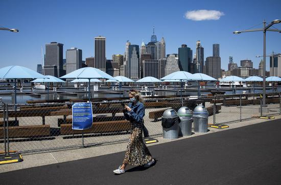 A pedestrian wearing a face mask walks at Brooklyn Bridge Park in New York, the United States, on April 28, 2020. (Photo by Michael Nagle/Xinhua)