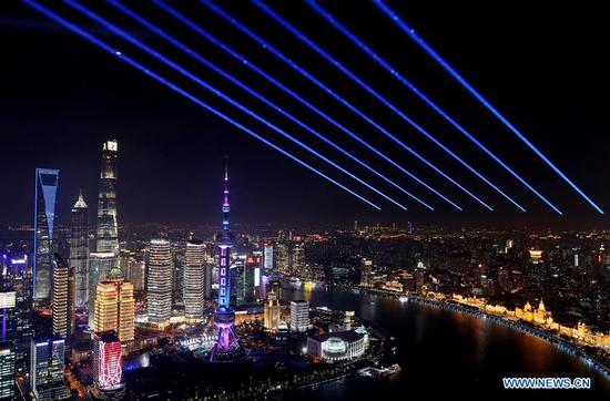 Beams of light are projected from the Sinar Mas Plaza in Shanghai, east China, Oct. 26, 2020. A light show will be held on Nov. 5 to celebrate the opening of the third China International Import Expo (CIIE), which will take place in Shanghai from Nov. 5 to 10. (Xinhua/Fang Zhe)